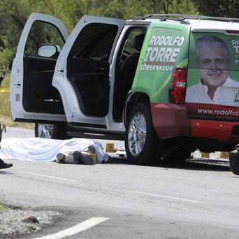 Army soldiers stand next to a campaign vehicle of the candidate for governor of the Mexican state of Tamaulipas, Rodolfo Torre, who was shot dead near Ciudad Victoria