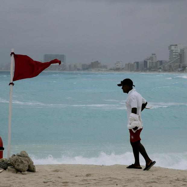 A life-guard stands next to a red flag meaning high hazard of high surf and/or strong currents as tropical storm Alex nears the region in the resort city of Cancun, Mexico