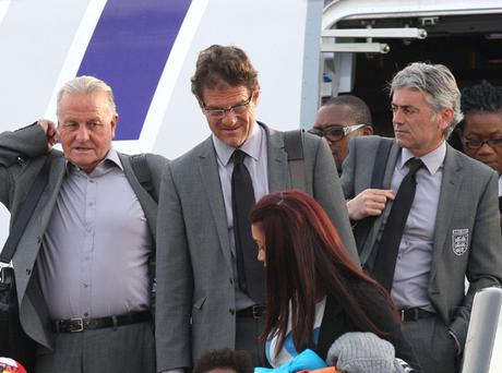 England manager Fabio Capello (centre) arrives at Heathrow Airport, London. The England team returned to the UK after a 4-1 defeat to Germany in the Round of 16 match in Bloemfontein, South Africa on Sunday