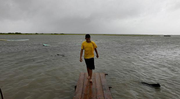 A man walks on a pier several hours before the arrival of Hurricane Alex, the first Atlantic hurricane of the year, in La Carbonera, north-eastern Mexico