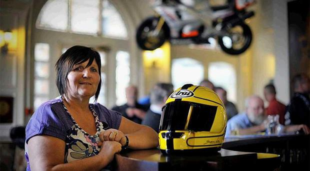 Linda Dunlop with one of her late husband's racing helmets at Joey's Bar in Ballymoney