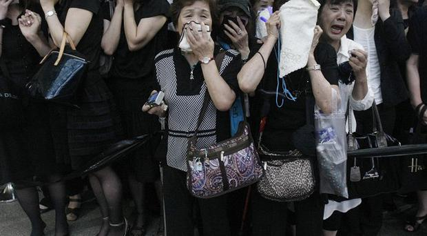 Fans cry as a hearse carrying the coffin of deceased South Korean actor and singer Park Yong-ha leaves a hospital in Seoul