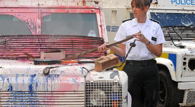 Grosvenor Road PSNI Area Commander Emma Mooney displays some of the weapons used during Saturday's trouble as well as a damaged Land Rover