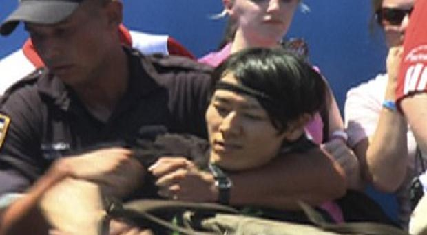 Six-time champion Takeru Kobayashi is taken into custody by New York police officers after jumping on stage at the end of a hot dog eating contest