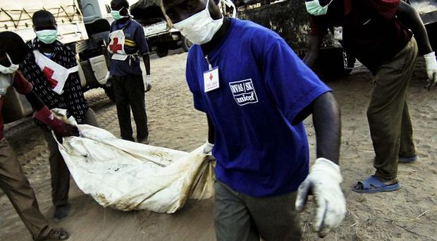 Volunteers of the Congolese Red Cross carry a body bag bearing a victim of oil tanker explosion in Sange