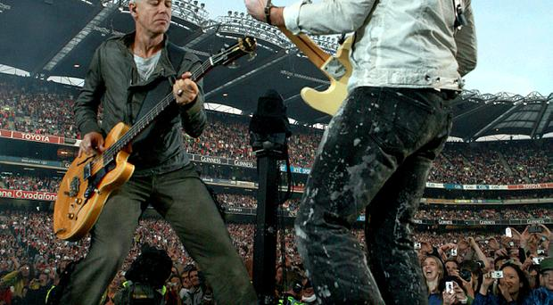 U2 bassist Adam Clayton (left, on stage with The Edge) is suing a bank and his accountants