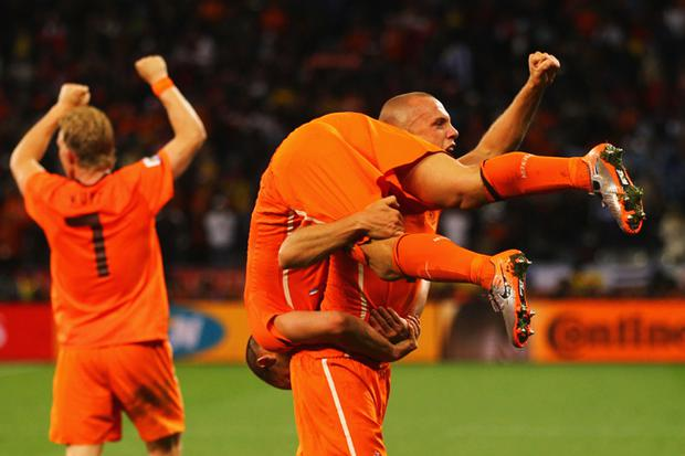 John Heitinga of the Netherlands carries Wesley Sneijder as they celebrate victory and progress to the final during the 2010 FIFA World Cup South Africa Semi Final match between Uruguay and the Netherlands at Green Point Stadium on July 6, 2010 in Cape Town, South Africa