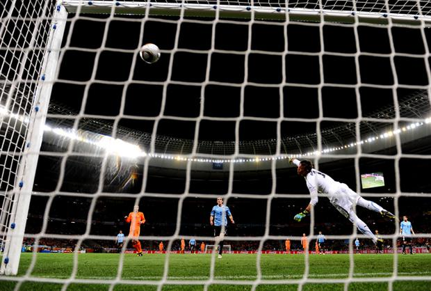 Fernando Muslera of Uruguay attempts to save the shot by Giovanni Van Bronckhorst of the Netherlands as he scores the opening goal during the 2010 FIFA World Cup South Africa Semi Final match between Uruguay and the Netherlands at Green Point Stadium on July 6, 2010 in Cape Town, South Africa