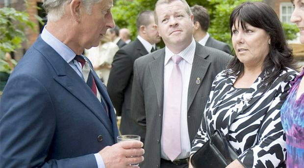 The Prince of Wales talks with Kate Carroll, wife of murdered PSNI officer Stephen Carroll, during a reception at Clarence House yesterday for the families of police officers killed while on duty