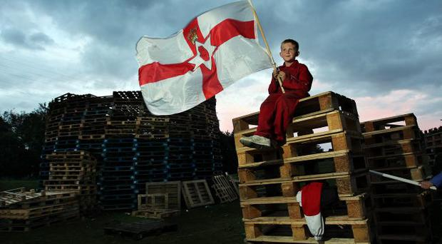 A young lad guards the bonfire at Avoniel