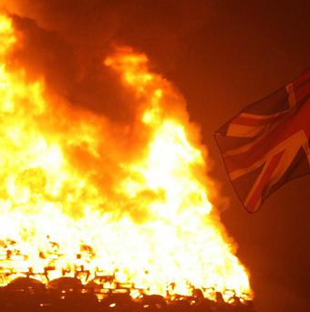 A Union Jack flies beside a bonfire on the Ballycraigy estate in Co Antrim the night before the Twelfth of July