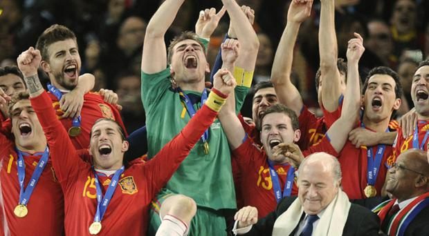 Spain goalkeeper Iker Casillas holds up the World Cup trophy as he and other team members celebrate, as South African President Jacob Zuma, front right, and FIFA president Sepp Blatter, second from right in front, look on