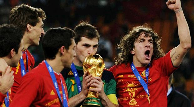 Iker Casillas of Spain kisses the World Cup trophy as the Spain team celebrate victory following the 2010 FIFA World Cup South Africa Final match between Netherlands and Spain at Soccer City Stadium on July 11, 2010 in Johannesburg, South Africa