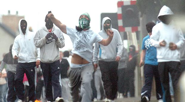 Masked youths riotiing in Lurgan last night as trouble continued throughout the day iin the republican Kilwilkee area