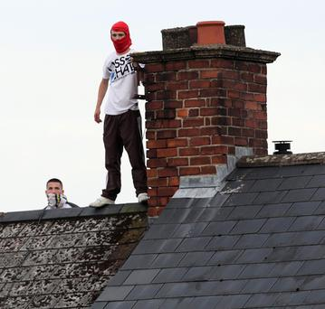 Nationalist youths stage a rooftop protest as an Orange Order parade passes the Ardoyne shops in North Belfast