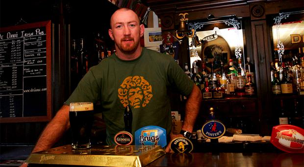Trevor Brennan behind the bar of the De Danu Irish pub which he owns in Toulouse