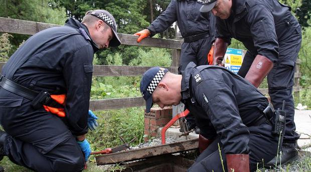 Police officers search drains near to the scene where gunman Raoul Moat took his own life