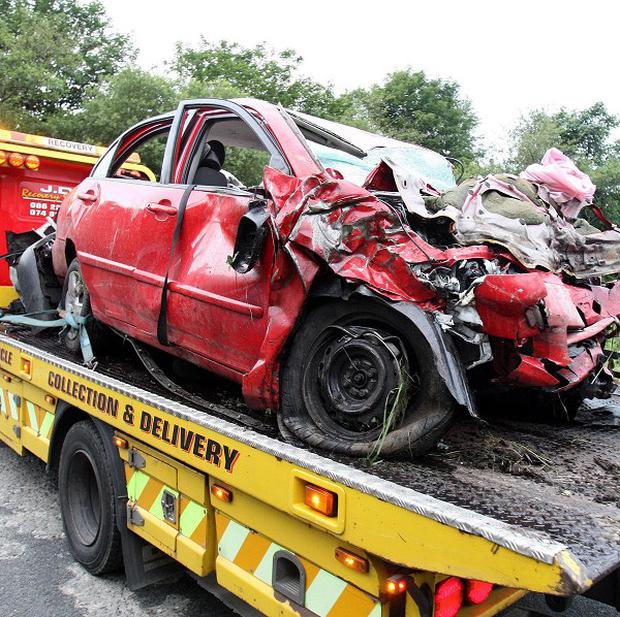 A red Toyota involved in the horror smash is removed from the scene