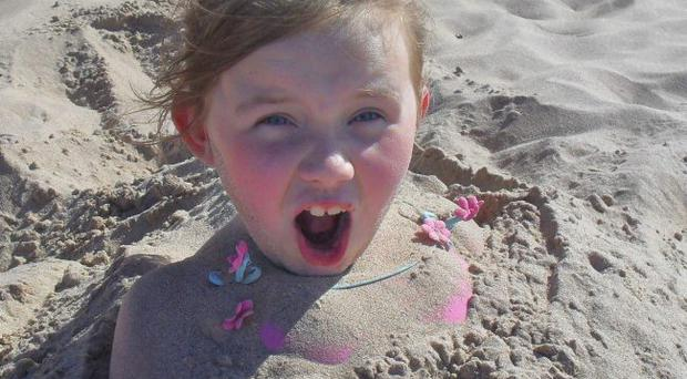 Beachy head: Alan Wilson snapped his daughter buried in sand during a day trip to Portrush