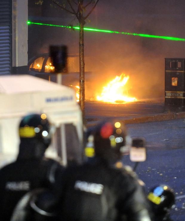 Rioters shine a green laser light to try to blind police officers during disturbances in the Ardoyne area of North Belfast