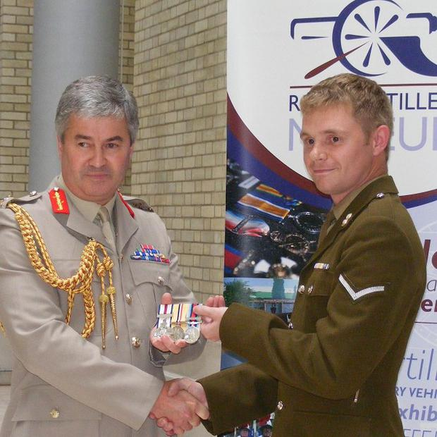 Lance Bombardier Gary Prout gives his Conspicous Gallantry Cross to Major General Richard Barrons