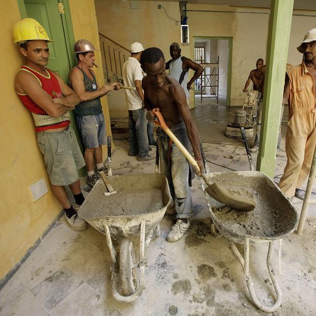 A construction team at work in Havana as Cuba's government warned one in five workers may face redundancy (AP)