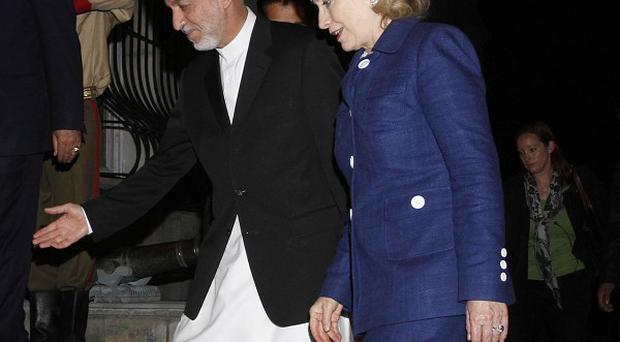 Afghan President Hamid Karzai escorts the US Secretary of State Hillary Clinton into the presidential palace in Kabul (AP)