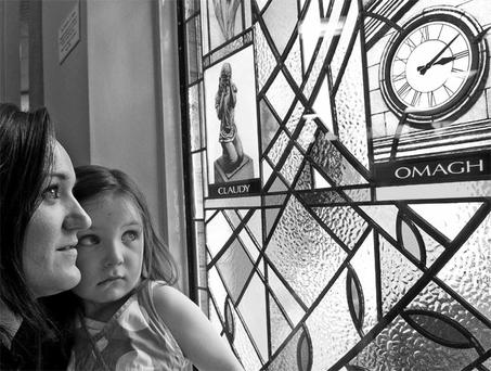 Claire Radford, whose brother Alan was killed in the Omagh bomb, examines a new stained-glass window in the town's library with her daughter Mia.