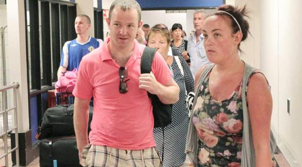 Holiday makers arrive home at Belfast International Airport from Dalaman in Turkey. Press Eye