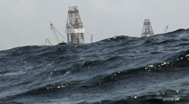 Waves partially obscure rigs drilling relief wells, at the Deepwater Horizon oil spill site in the Gulf of Mexico (AP)