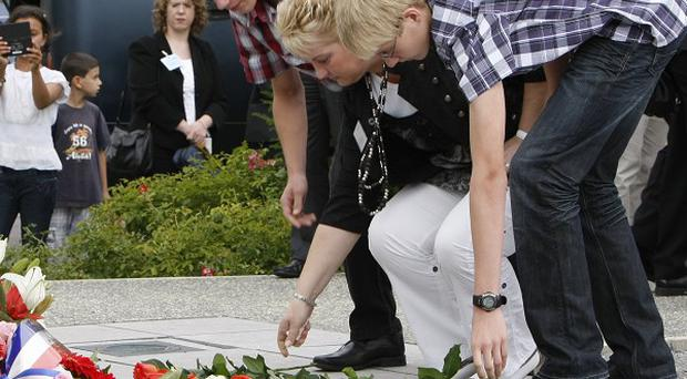 Family of victim from the Concorde jet crash lay flowers at the site of the crash in Gonesse, north of Paris (AP)
