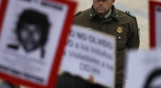 A police officer looks on as people hold portraits of dissidents killed by former General Augusto Pinochet in Chile (AP)