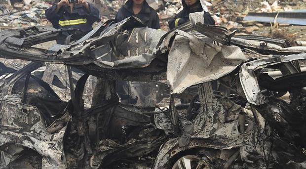 Firemen check the wreckage of a car after a factory explosion in Nanjing, in Jiangsu province (AP)