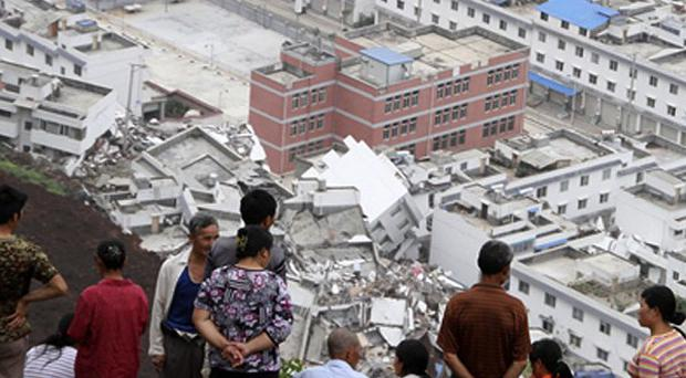Locals look at the scene of a landslide in Hanyuan County, China (AP)