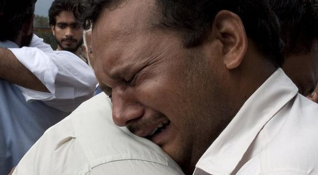 Relatives mourn the deaths of their family members killed in a plane crash, outside a local hospital in Islamabad. (AP)
