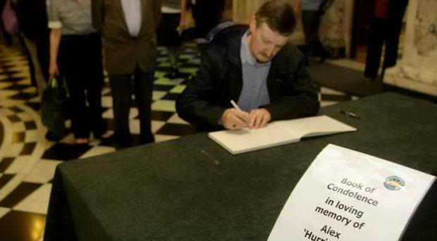 People line up to sign the book of condolence for Alex Higgins