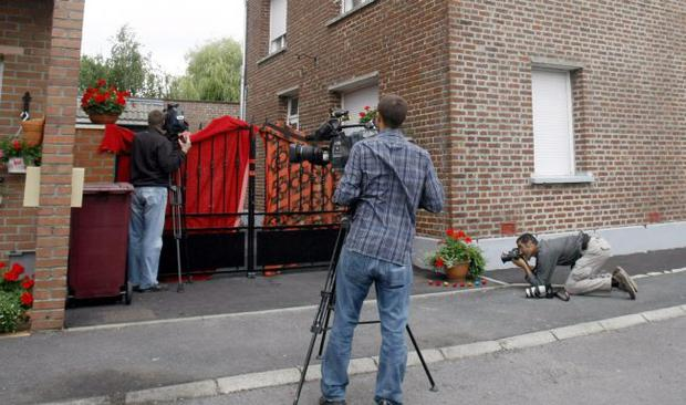 Reporters are seen in front of the house where French police found the corpses of eight newborn babies, in Villers-au-Tertre, northern France, Thursday, July 29, 2010.