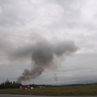 A plume of smoke rises from Elmendorf Air Force Base in Anchorage, Alaska, after a military cargo plane crashed