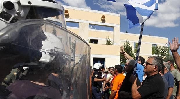 Protesting truck drivers shout anti-government slogans outside the Ministry of Transport in Athens (AP)