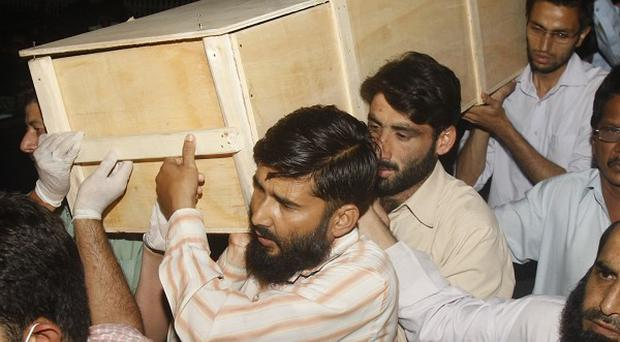 Men carry the body of a passenger at a hospital in Islamabad after the plane crash (AP)