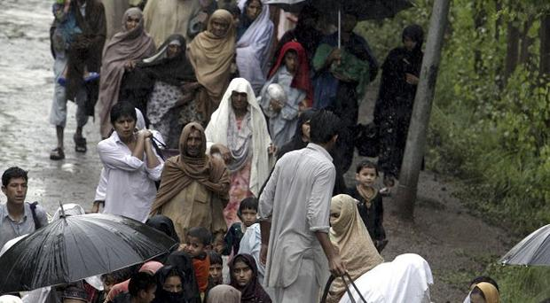 Pakistani villagers move to a safe place from a flood-hit village near Nowshera, Pakistan