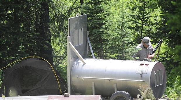A marksman patrols the area where a man was killed by a bear at the Soda Butte camp site in Wyoming