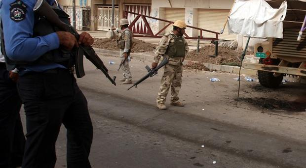 Iraqi security forces inspect the scene of an attack on a checkpoint in Baghdad