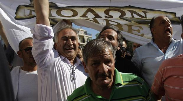 Union leader Giorgos Tzortzatos, second left, shouts anti government slogans with other striking truck drivers (AP)