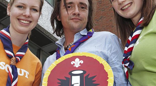 Richard Hammond receiving his Scientist Birthday Badge from two Explorer Scouts