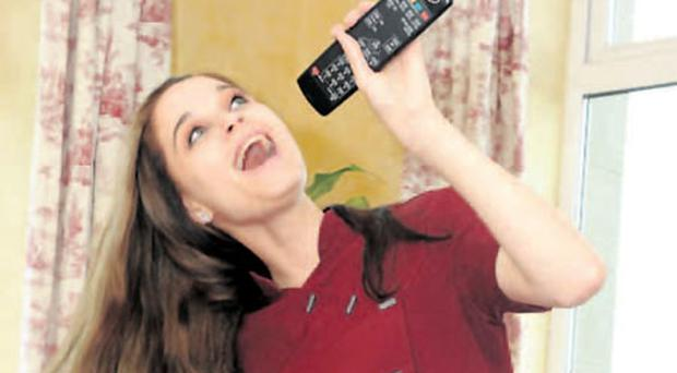 Star turn: Vierka Bierkova gives a mock performance with a TV remote control while at work in the Culloden