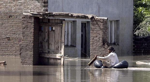 A villager uses an inflated tube to reach his flooded house on the outskirt of Peshawar, Pakistan (AP)