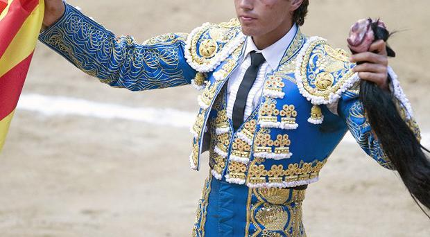 Bullfighter Miguel Tendero holds a Catalan flag and a bull's tail during the first bullfight in Barcelona after the ban was passed (AP)
