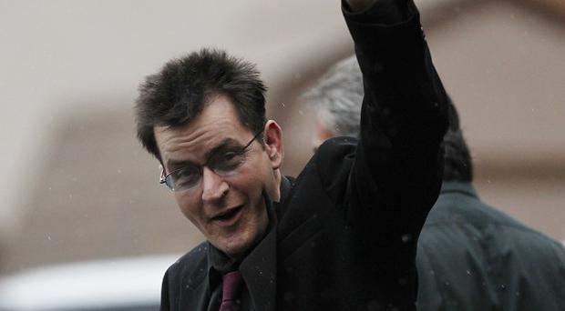Charlie Sheen waves as he leaves the the Pitkin County Courthouse in Aspen