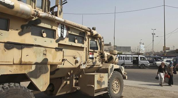 An soldier stands guard at the scene of an attack on a checkpoint in Baghdad (AP)